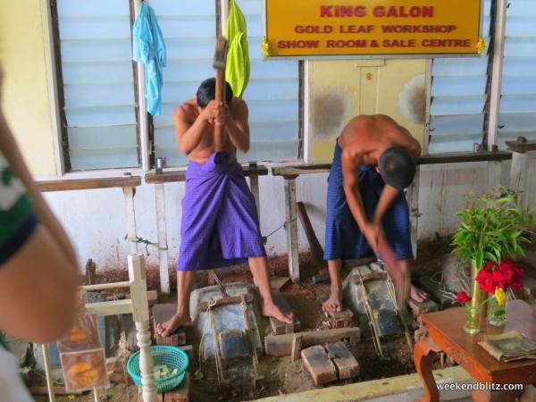 Workers at the gold leaf workshop hammering gold